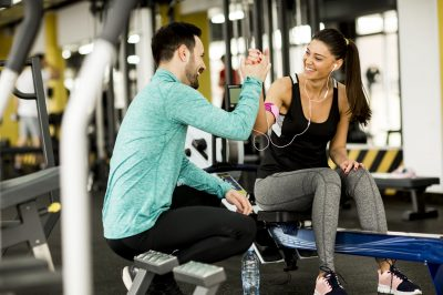 Woman exercise in a gym with the help of her personal trainer
